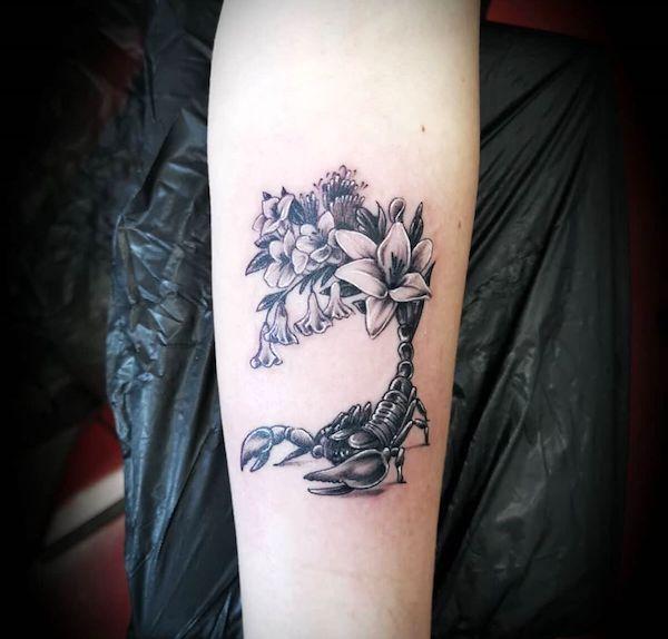 A Scorpio tattoo with flowers by @el_loco_tat2 - Scorpio tattoos for women that are pure dark aesthetics