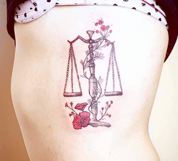 An elegant floral rib tattoo by @shushu_tattoo - Libra symbol and constellation tattoos